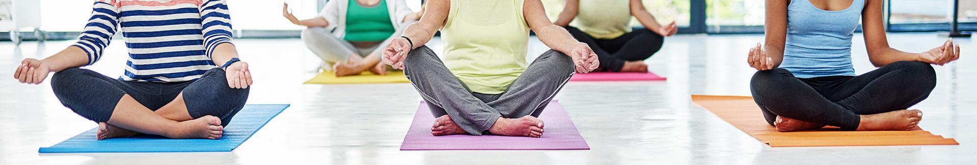Women on floor mats practicing yoga